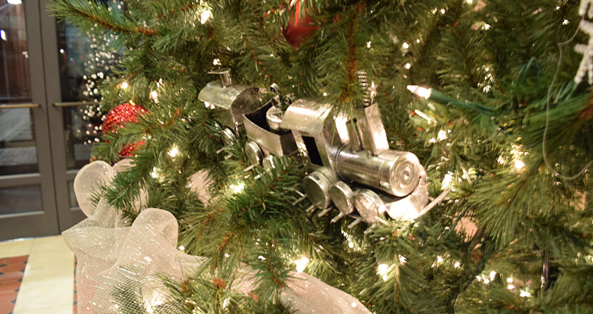An image of a Christmas tree with train ornaments