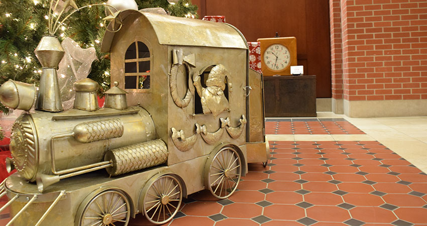 An image of a large train model placed at the base of a Christmas tree