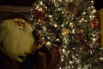 An image of a Christmas tree decorated with ornaments and lights and a stuffed Santa Clause