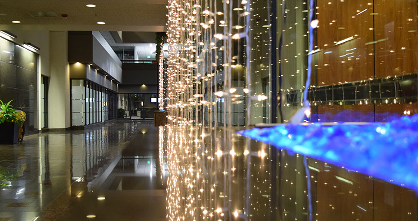 An image of holiday lights hanging inside of a corporate building's atrium
